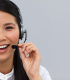 Half portrait of an asian secretary with earpiece. Speaking against whit background Stock Photography