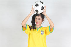 Half Portrait Beautiful woman hold ball over her head with weari. Image Half Portrait Beautiful woman hold ball over her head with wearing Brazil football top Royalty Free Stock Image