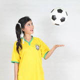 Half Portrait Beautiful woman throw up ball  with wearing Brazil. Image Half Portrait Beautiful woman throw up ball  with wearing Brazil football top Royalty Free Stock Images