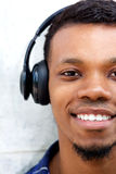 Half portrait of smiling man with headphones listening to music Stock Photo