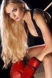 Woman posing in red boxing gloves. Half portrait of young blonde woman with long hair, dressed in black sports bra, pink shorts and red boxing gloves, looking to Stock Photo