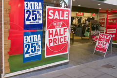 Half Price Discount Sale. Posters in a high street store window advertising a  better than half-price discount sale Stock Images