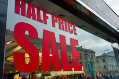 Half price sale sign in a shop window. Half price sale sign in a shop window, with a reflection of the street Royalty Free Stock Photos