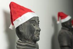 Half profile of Chinese terracotta warrior statue wearing santa hat Stock Image