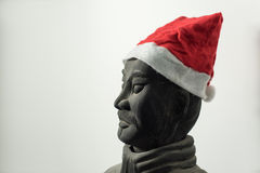 Half profile of Chinese terracotta warrior stature wearing santa hat. Face, isolated on white background Royalty Free Stock Photos