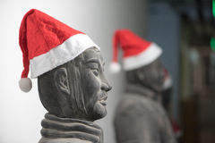 Half profile of Chinese terracotta warrior stature wearing santa hat. Upper body, with more statues in the background, selective focus Stock Photography