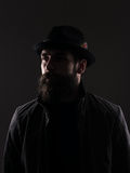 Half profile of serious bearded man in black hat looking away. Low key dark shadow portrait over black background royalty free stock photo