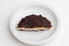 Half puffed rice cake with peanut butter and chocolate on white. Plate on white table Stock Photos