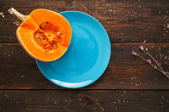 Half of pumpkin on blue saucer flat lay void. Top view on wooden kitchen table with half of fresh squash, free space. Cooking, recipe, seasonal vegetarian Royalty Free Stock Image