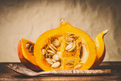 Free Half Pumpkin With Seeds And Wooden Cooking Spoon At Natural Beige Background, Front View. Healthy Autumn Seasonal Food Royalty Free Stock Photos - 97889728