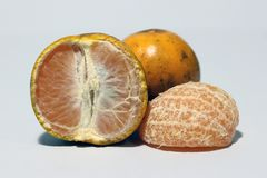 Half and quarter of peeled orange and one orange does not peel isolated on white background. Orange is a round juicy citrus fruit with a tough bright reddish royalty free stock photos