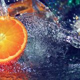 Half of raw organic juicy orange with water splashes, selective focus. Healthy lifestyle, dietary eating, refreshing summer drink Royalty Free Stock Photography