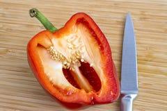 Half of red bell pepper freshly sliced and sharp knife lying on Stock Photo