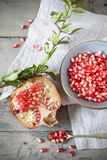 Half red juicy pomegranate with branch and grains on bowl on wooden table Royalty Free Stock Images
