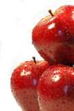 Half red pile. Close up view of three red apples on the right half side of the screen, with drops of water, isolated on a white background Stock Images