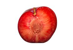 Half red plum. Juicy half of a large red plum isolated on white background royalty free stock images