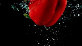Half of red sweet pepper falls into water close up super slow motion shot stock footage