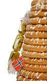 Half Ring Cake & Cracker. Traditional Norwegian marzipan ring cake - kransekake - seen from side with cracker and Norwegian flag. Isolated with clipping path Royalty Free Stock Photo