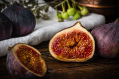 Half ripe and juicy fig lying on rustic table Royalty Free Stock Photo