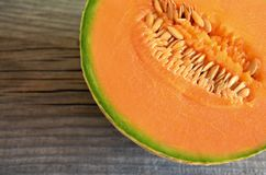 Half of ripe organic cantaloupe melon muskmelon, mushmelon, rockmelon on old wooden table. Selective focus royalty free stock images