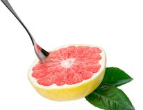 Half ripe organic grapefruit with spoon isolated. Royalty Free Stock Images