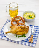 Half roast chicken, beer, pretzel and potato salad Stock Photos