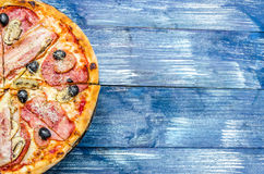 Half a round pizza with meat, olives, cheese and mushrooms, on a blue denim background royalty free stock image