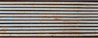 Half-rusted rainfall lattice looking like horizontal  metal stripes. Texture or background stock photo