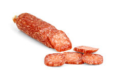 Half of salami sausage and some slices near. Isolated on the white background Royalty Free Stock Photo