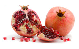 Half and scattered grains of a pomegranate. On a white background Royalty Free Stock Photo