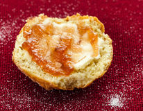 Half scone with butter and jam on red tablecloth Royalty Free Stock Images
