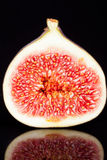 Half of  sectioned fresh fig on black background-macro Stock Image