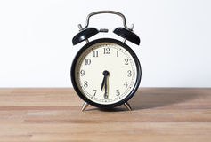 It is half seven o`clock. The time is 6:30 am or pm. it is half past six. A retro clock isolated on a wooden table and white background Royalty Free Stock Image