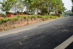 Half-shaded hillside blacktop driveway on sunny day Stock Images