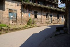 Half-shaded street between aged dwelling buildings in sunny summ Royalty Free Stock Photography