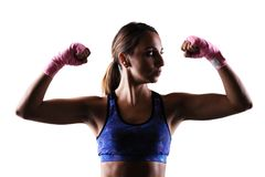 Half silhouette girl kickboxer. Girl kickboxer with pink hand wraps, showing muscles, backlit portrait Stock Image