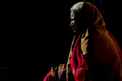 Half Silhouette of Rajasthani Woman. A half silhouette of an old Rajasthani lady siting in a dark space with a little of light, Rajasthan, India, 14th of March Royalty Free Stock Photos