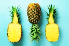 Half slice of fresh pineapple and whole fruit on blue background. Top View. Copy Space. Bright pineapples pattern for Stock Photography