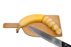 Half sliced banana on board. With chef knife Royalty Free Stock Images