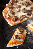 Half and slices of pizza with mushrooms and cheese Royalty Free Stock Photography