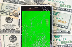 Half of Smartphone with broken screen on money background Royalty Free Stock Photos