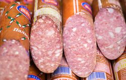 Half-smoked sausages showed at refrigerated store window stock images