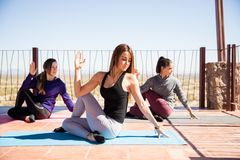 Half spinal twist pose in yoga class. Group of young hispanic women doing the half spinal twist pose in a yoga studio Stock Images