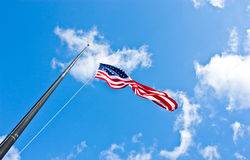 Half staff American flag. American flag on a blue sky during a windy day Royalty Free Stock Images