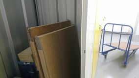 Half a storage unit with a blue moving trolley outside. A collection of boxes with manuals bags and decorating tables stacked up against the corrugated metal stock photography
