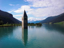 Half-submerged church bell tower with mountains (wide shot) Stock Photos