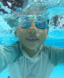 Half submerged 4 year old asian boy playing in pool Royalty Free Stock Photos