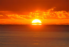 A half sun shows over ocean at sunrise. A half sun peaks over the ocean horizon, pearing through rows of gold lined orange cumulus cloud, and the early offerings Stock Photos