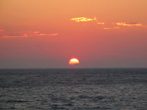 Half-Sunk Sun. Sunset in the Aegean Sea, Greece, with the sun already started sinking in the sea stock photography