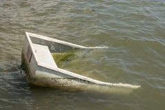 Half sunken boat in sea. Small boat or dingy half sunk and submerged in the sea at Emsworth, Hampshire, England royalty free stock photos